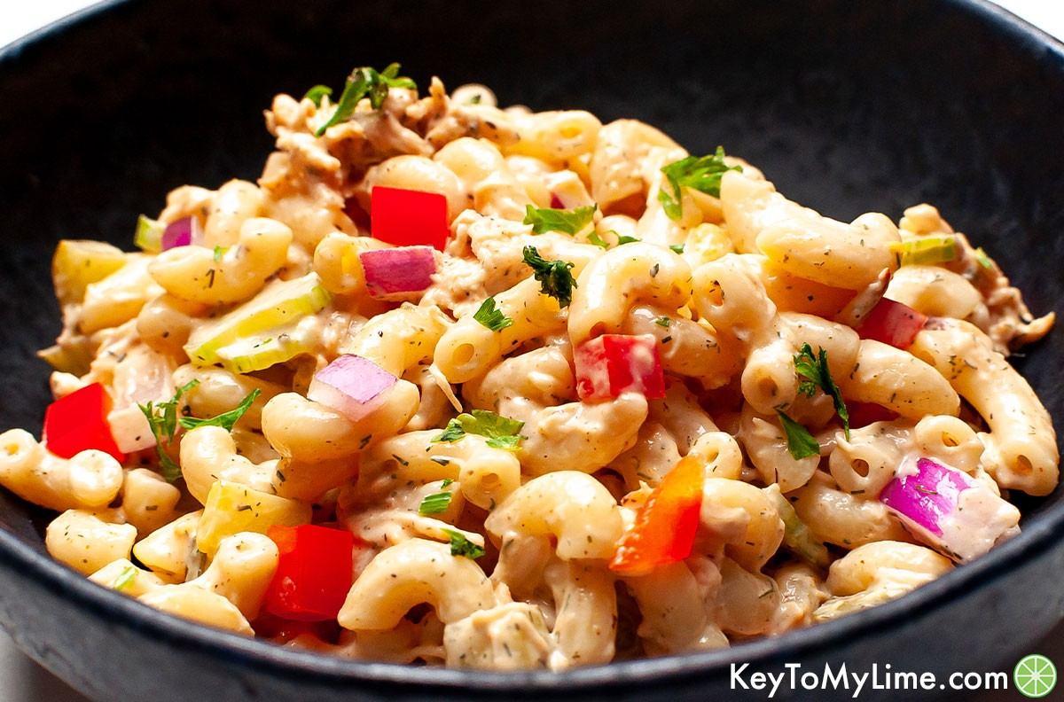A small bowl of chicken macaroni salad with the light glistening off of it.