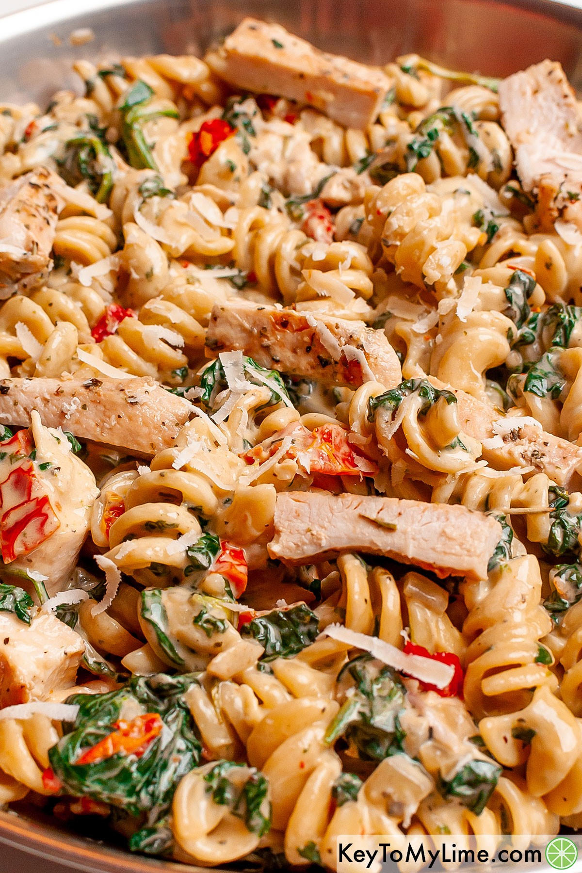 Tuscan chicken pasta in a silver skillet.