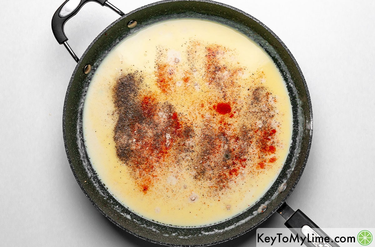Adding powdered spices to mac and cheese sauce.