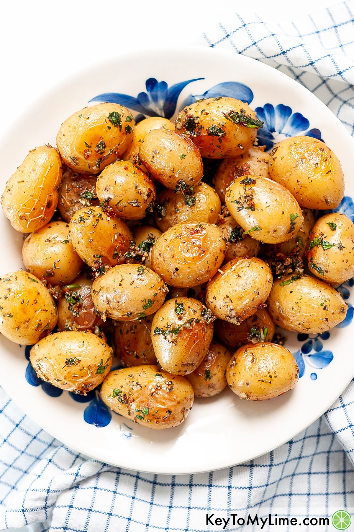 A blue and white bowl filled with roasted baby potatoes.