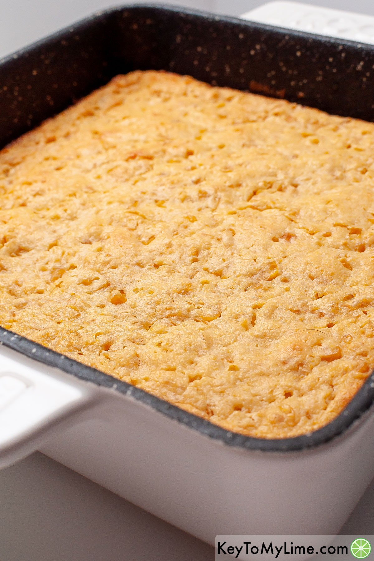 A close up image of corn casserole in a baking dish.