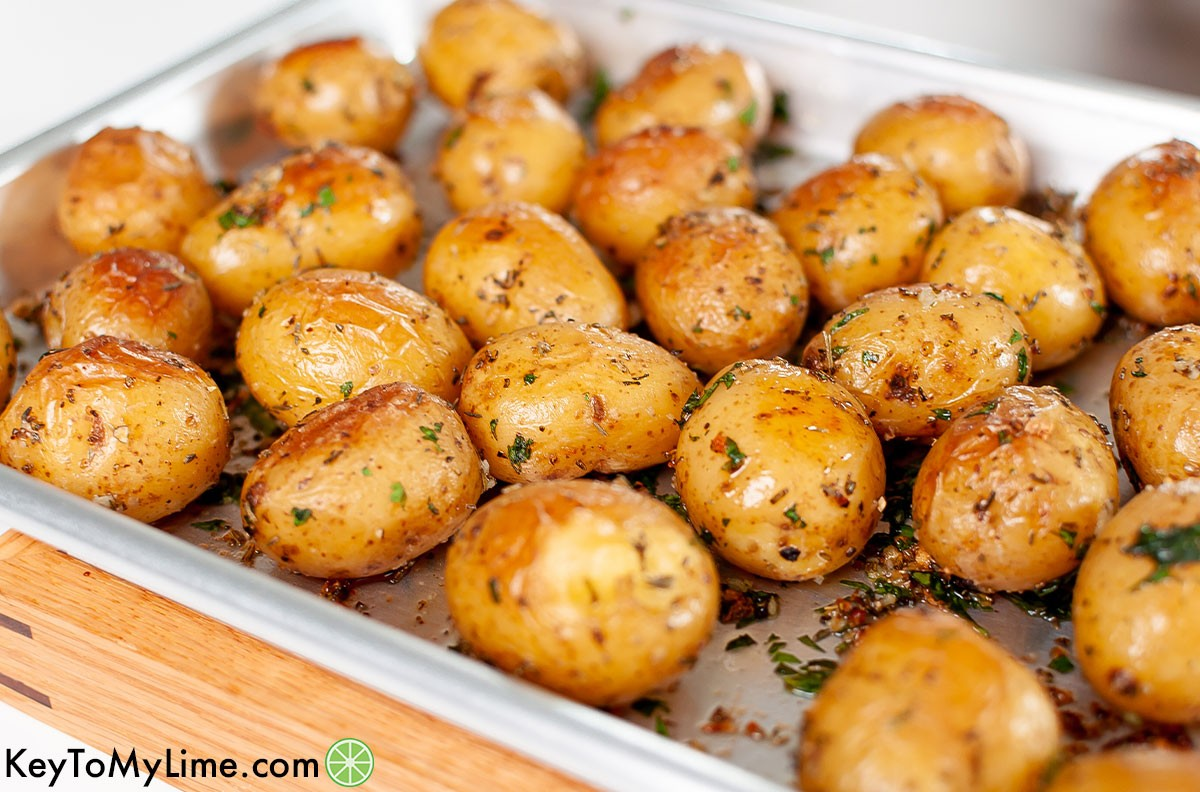 A side image of roasted baby potatoes on a baking tray.