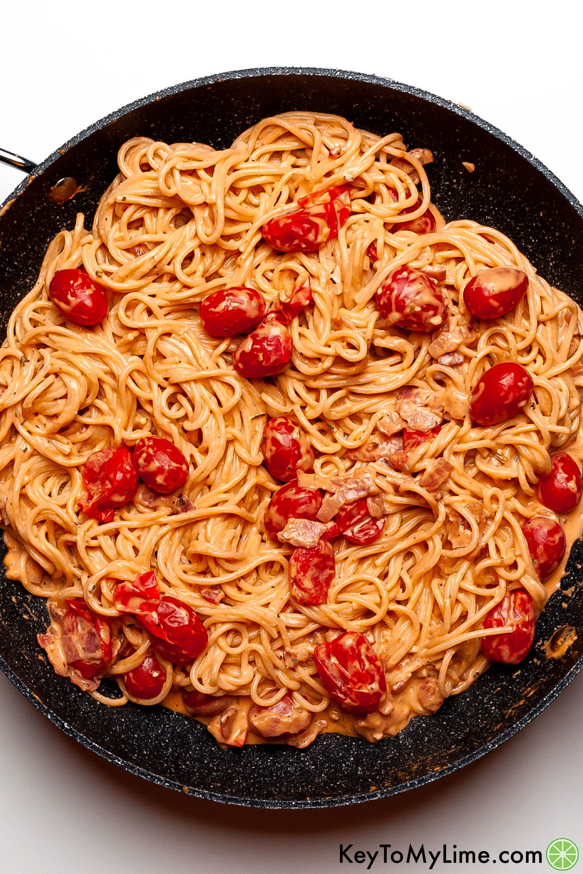 Creamy bacon pasta with tomatoes in a skillet.