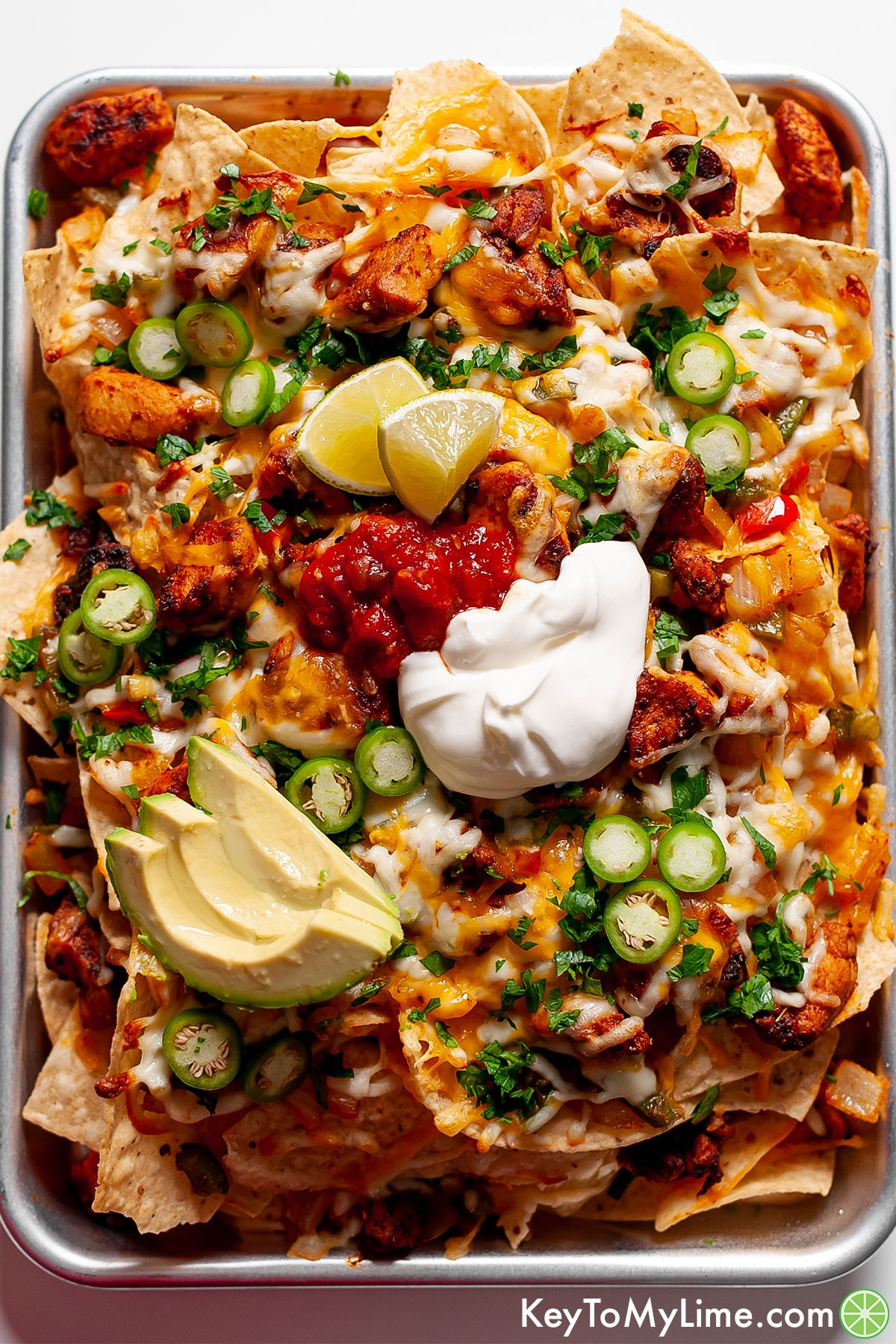 A tray of fajita nachos topped with lime wedges, salsa, and sour cream.