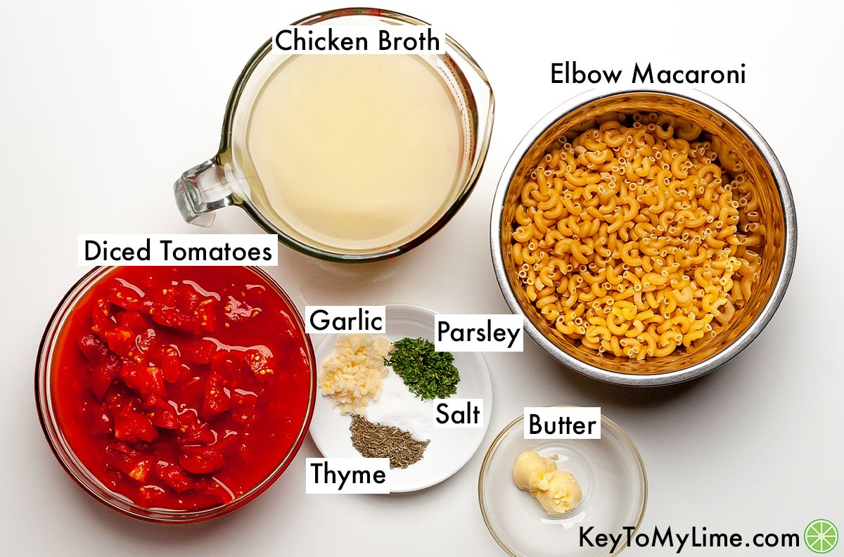 Macaroni and tomatoes ingredients in individual containers and labeled.