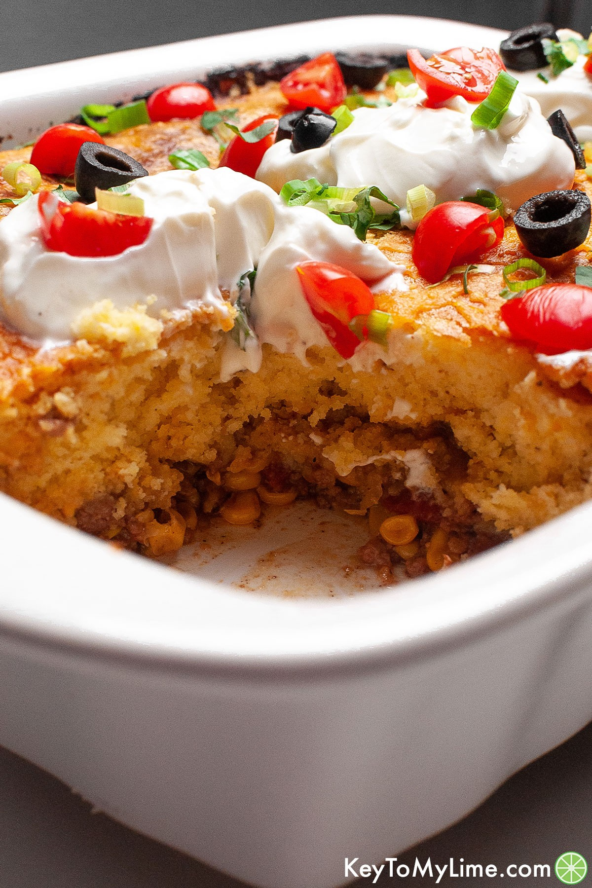 A casserole dish with a serving of Mexican cornbread casserole missing.