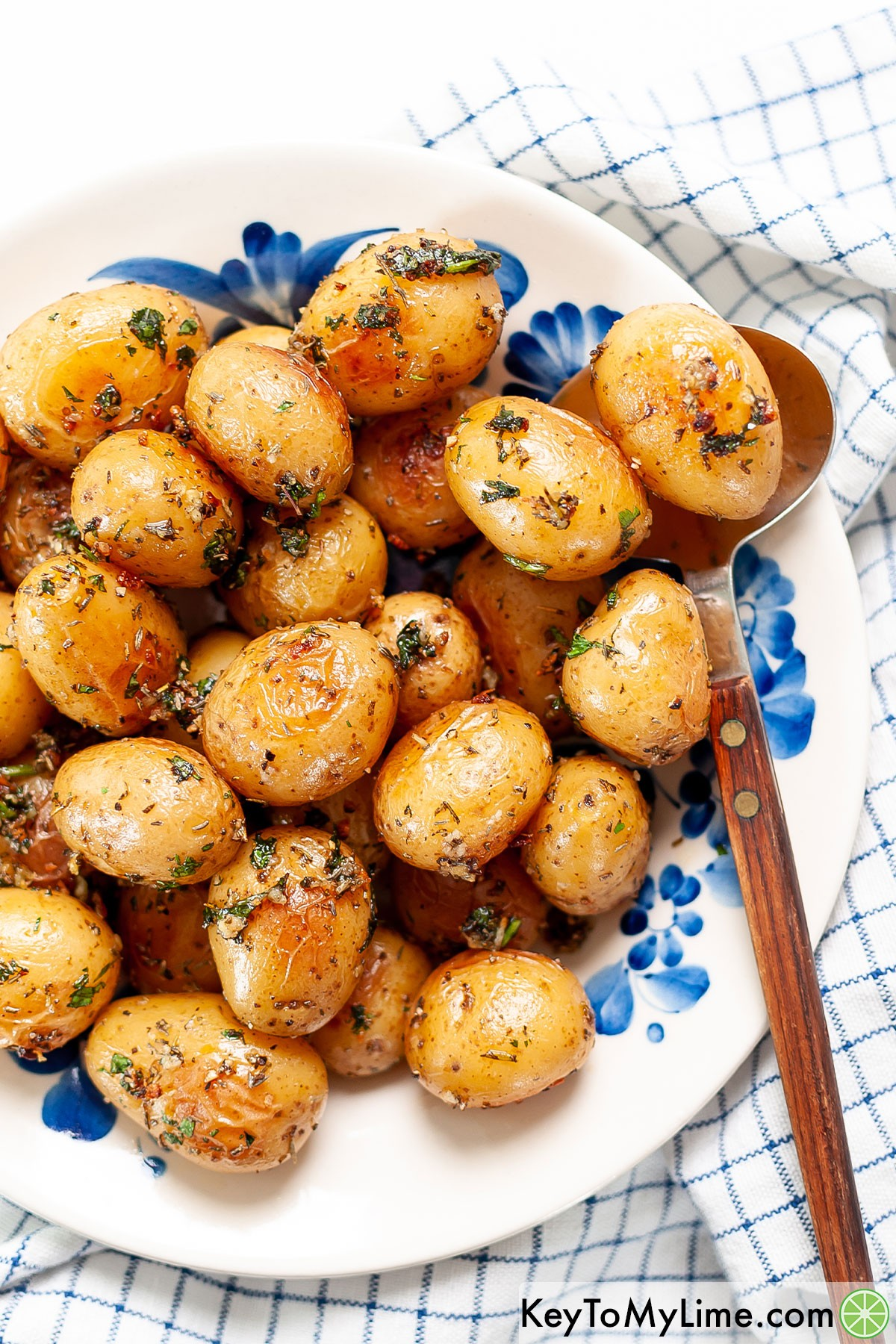 A bowl of roasted baby potatoes with a serving spoon underneath a potato.