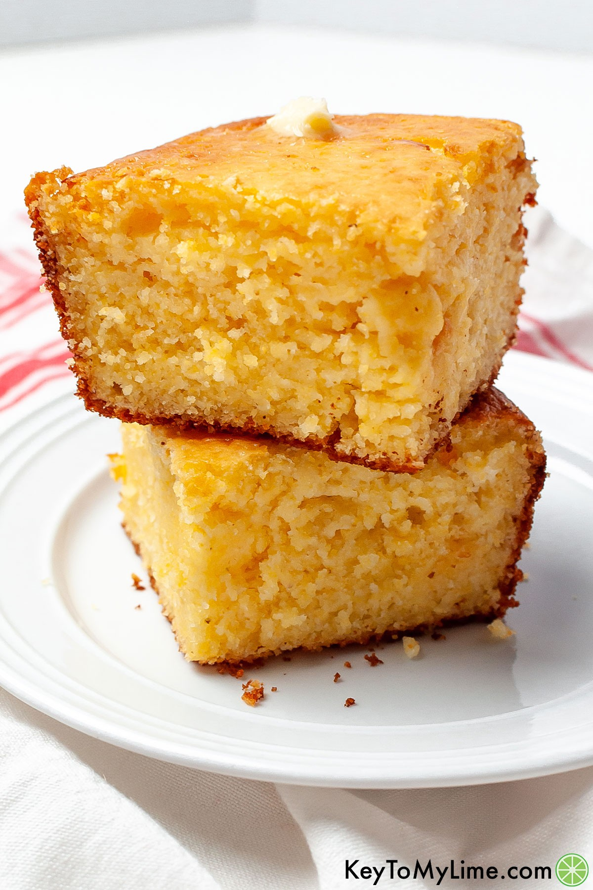 Two pieces of the best Jiffy cornbread stacked on a plate.
