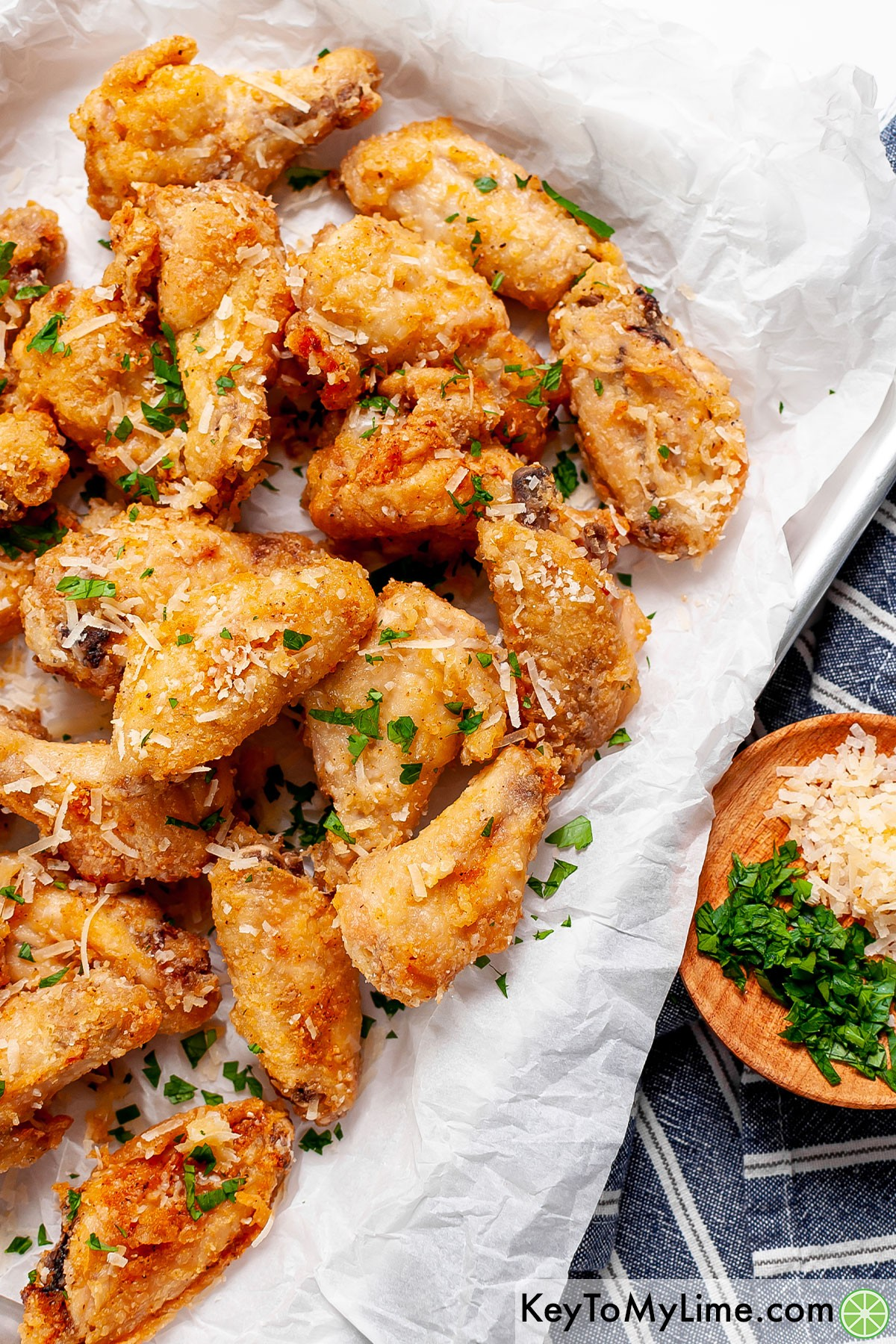 A tray of garlic parmesan wings against a blue striped napkin.