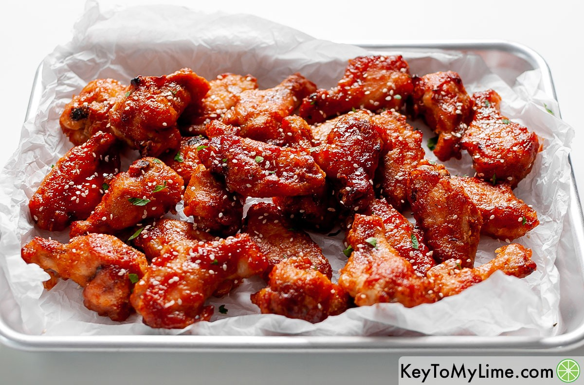 A tray of sweet and sour wings with light glistening off of them.