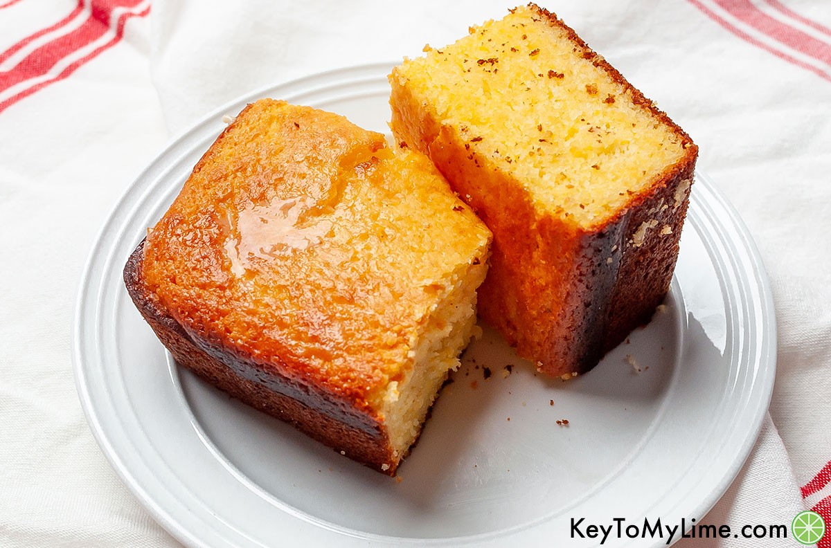 Two pieces of Jiffy cornbread with melted butter on a plate.