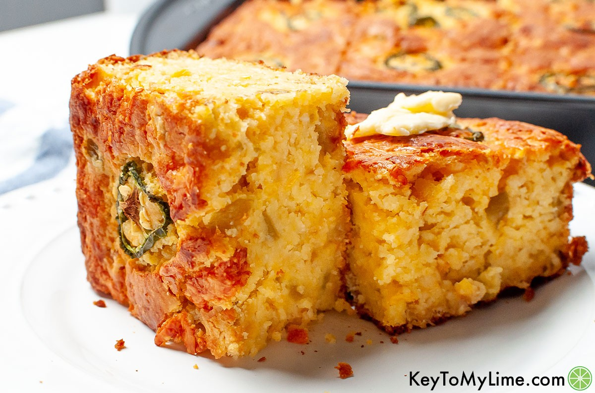 Two slices of Mexican cornbread on a plate with a dab of butter on top of one.