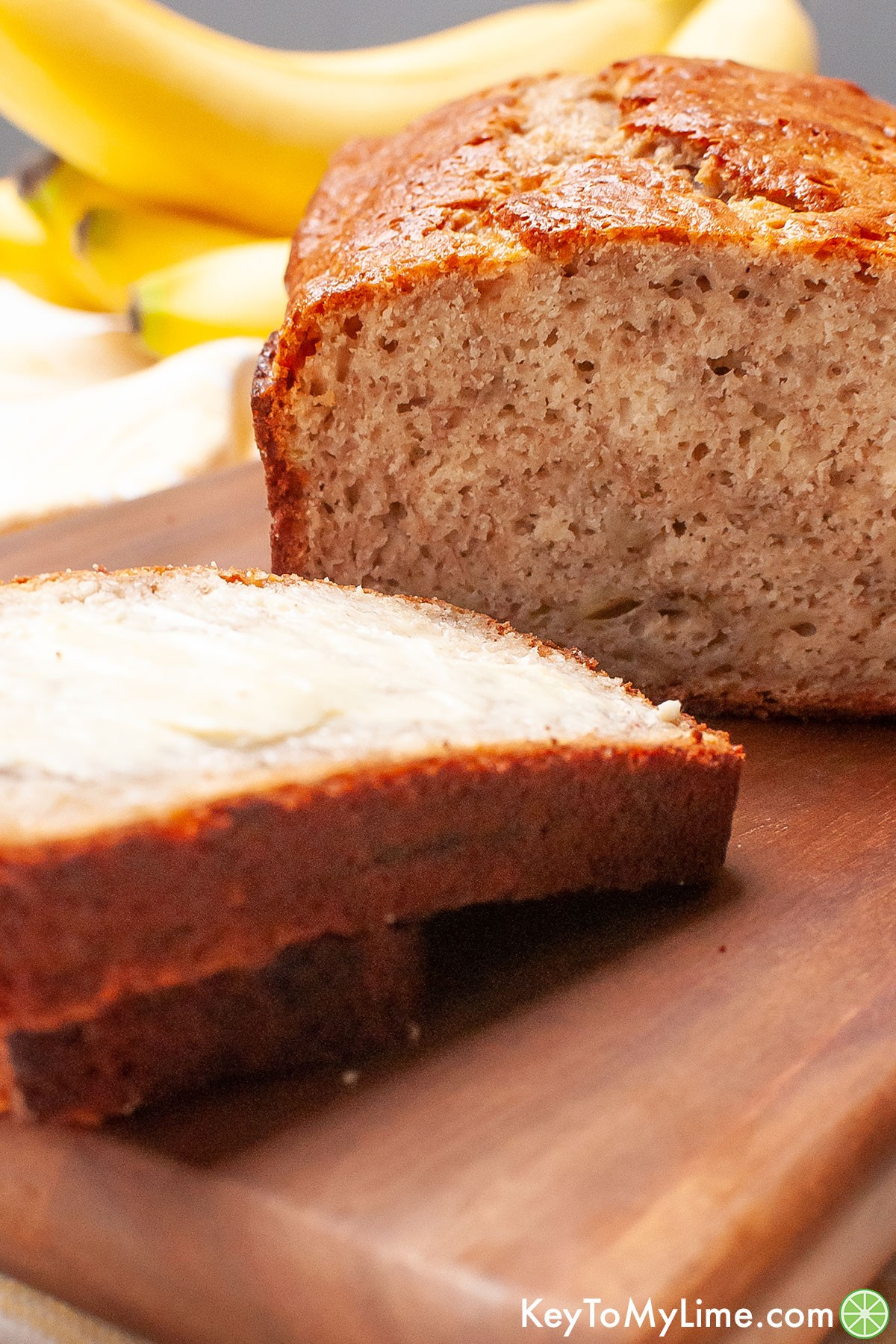 A loaf of banana bread with buttered slices on a wood board.