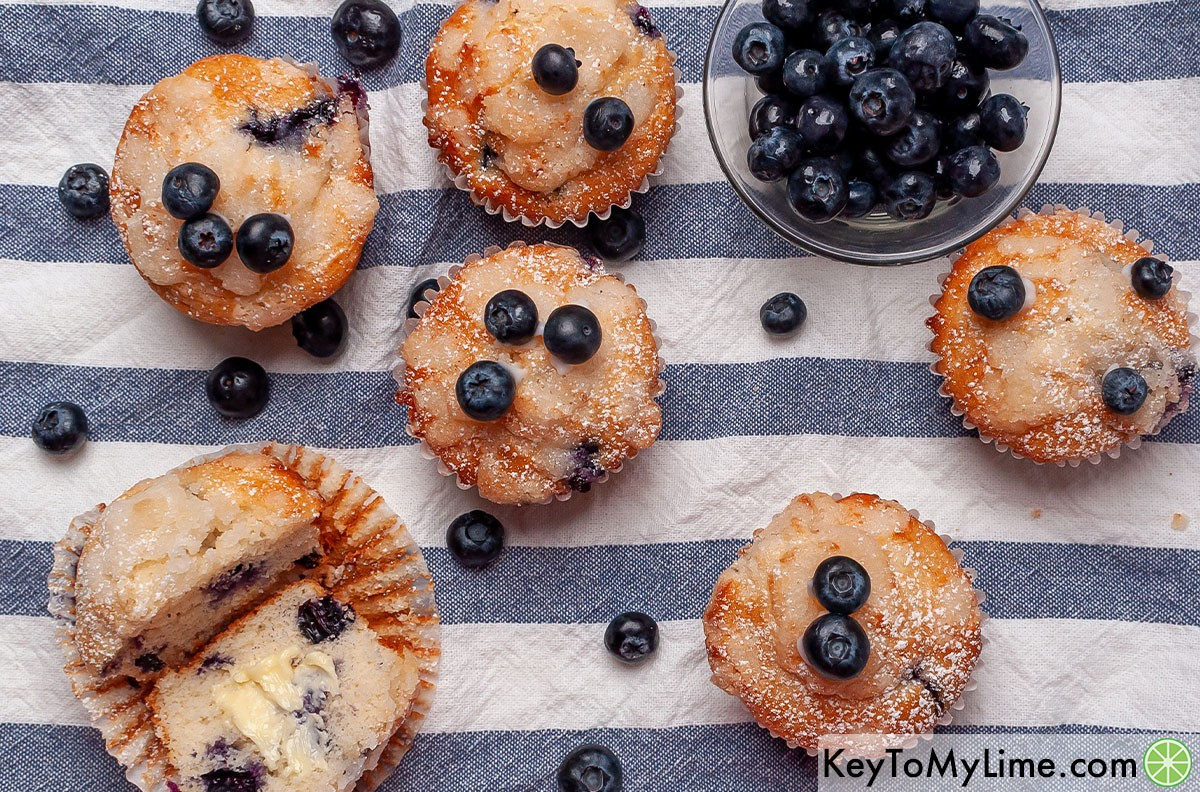 An overhead image of blueberry muffins on a blue and white napkin.