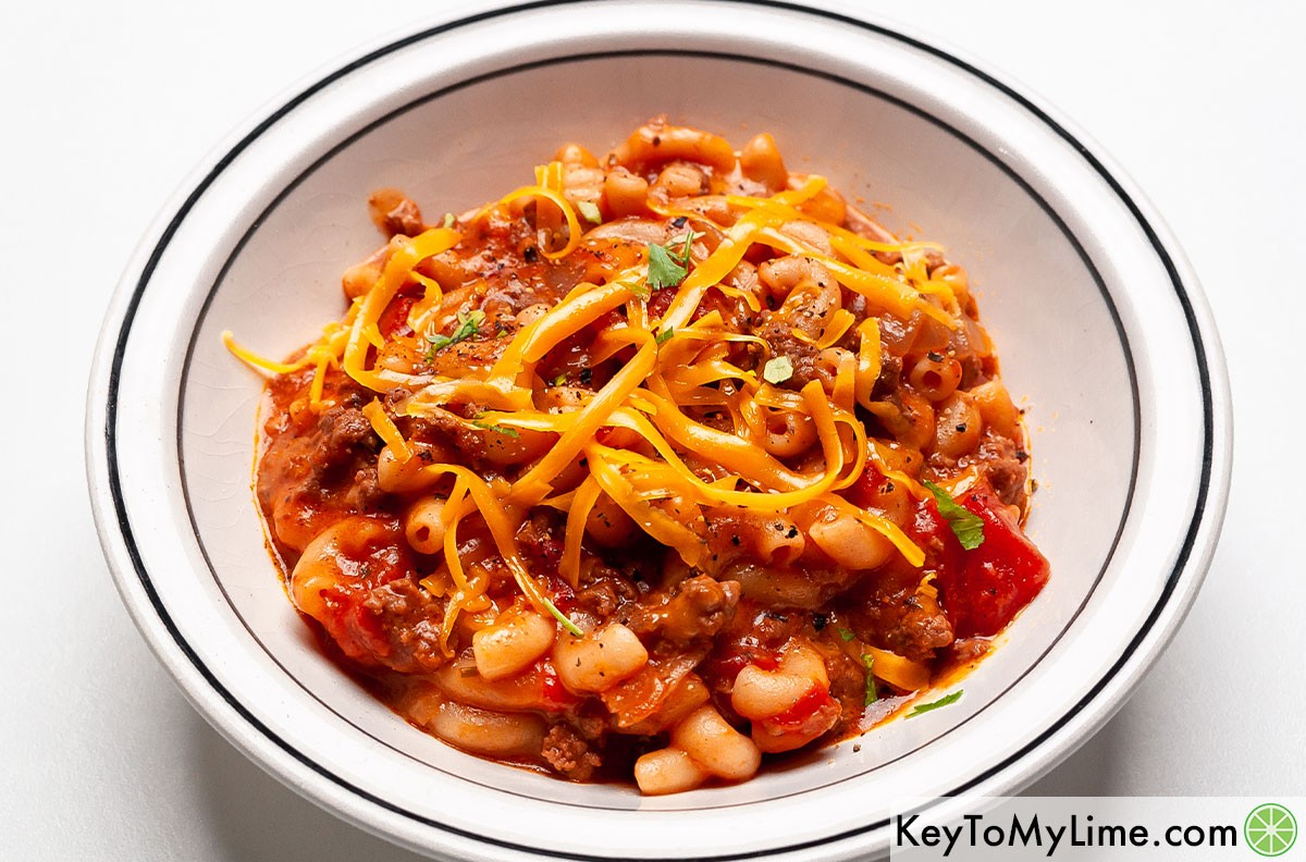 A bowl of American goulash topped with shredded cheddar cheese.
