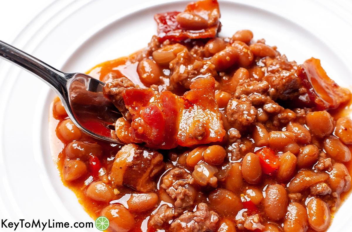 A fork taking a bite of Southern style baked beans.