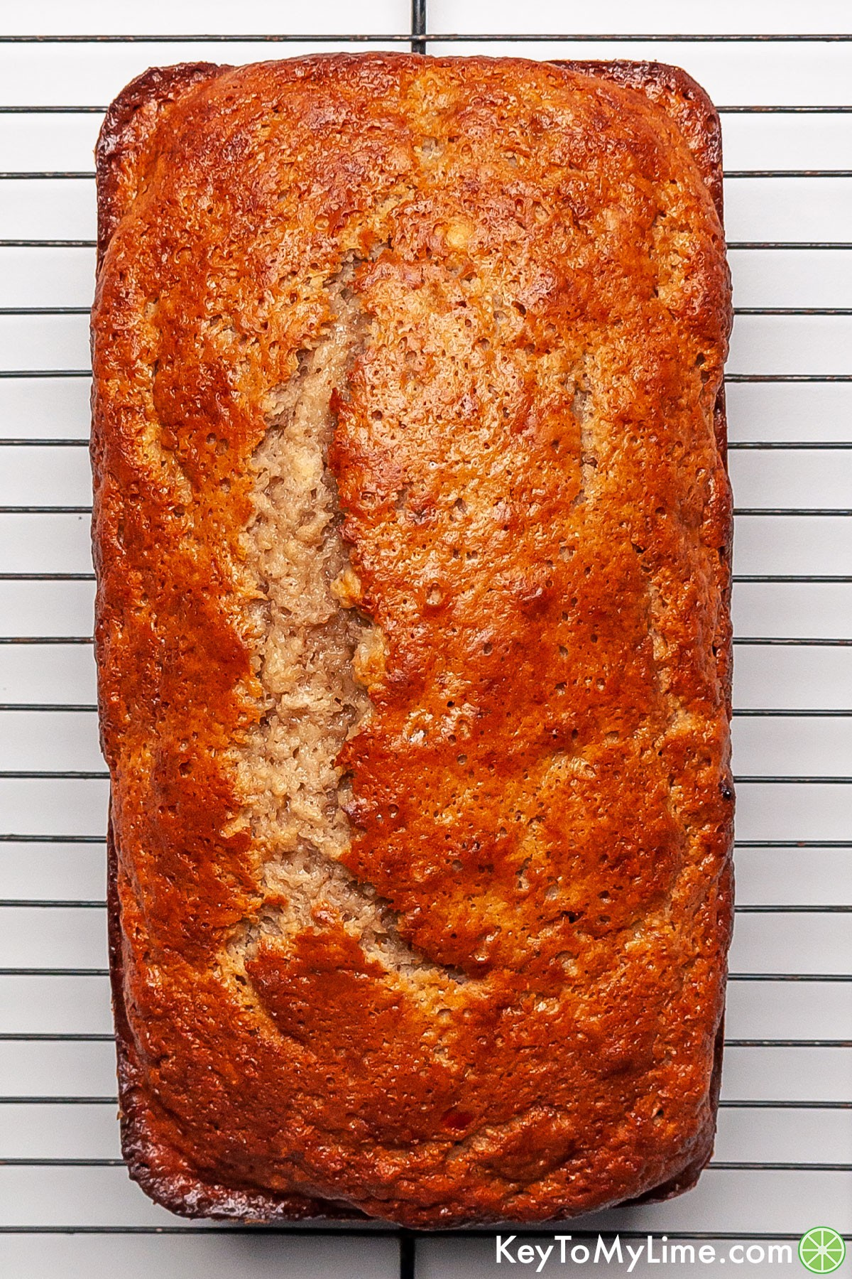 A loaf of banana bread cooling on a wire rack.