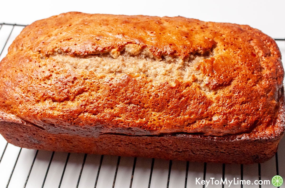A loaf of banana bread on a wire cooling rack.