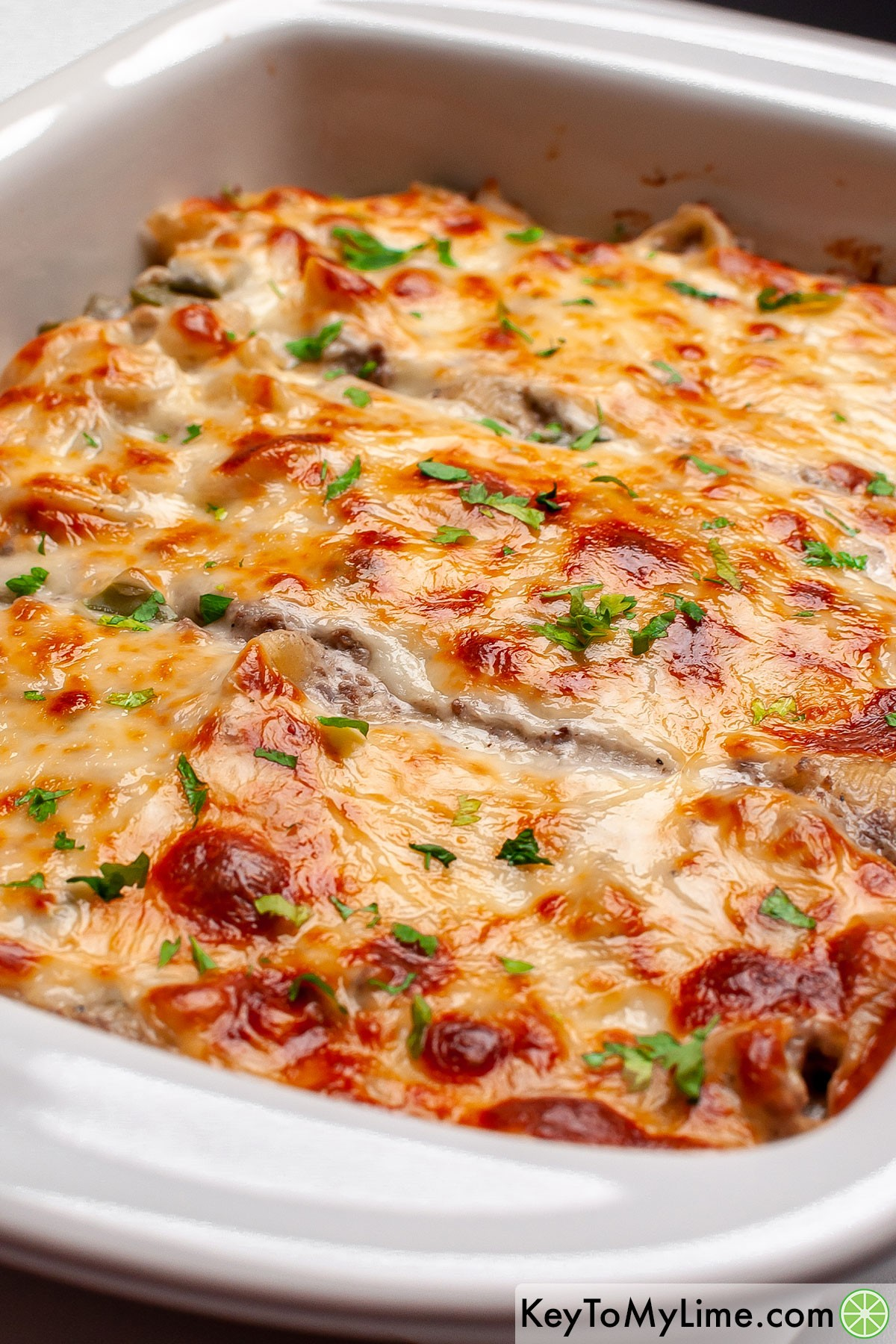 A cheesy Philly cheesesteak casserole in a white baking dish.