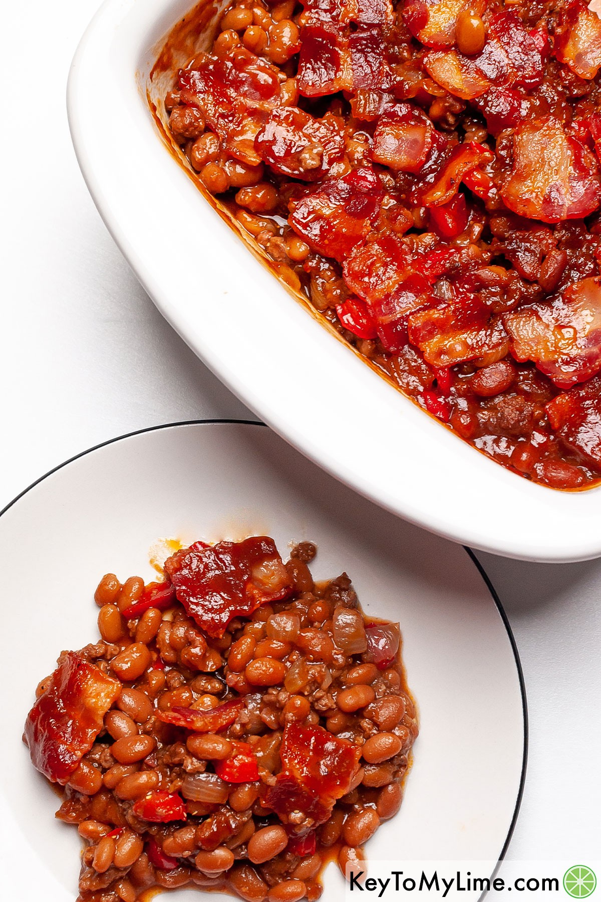 A serving of baked beans on a plate next to the casserole dish.