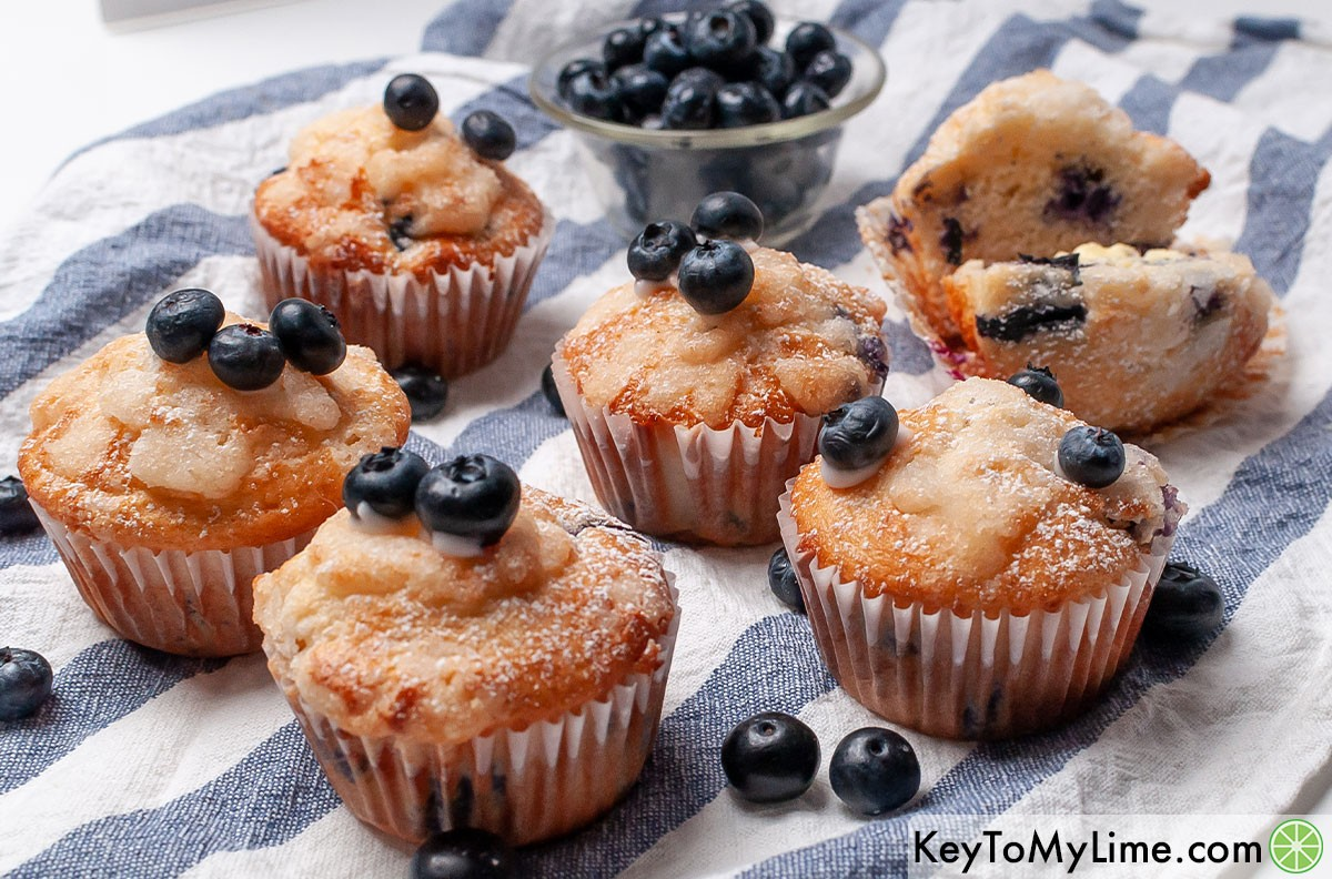 Six Bisquick blueberry muffins with streusel topping surrounded by fresh blueberries.
