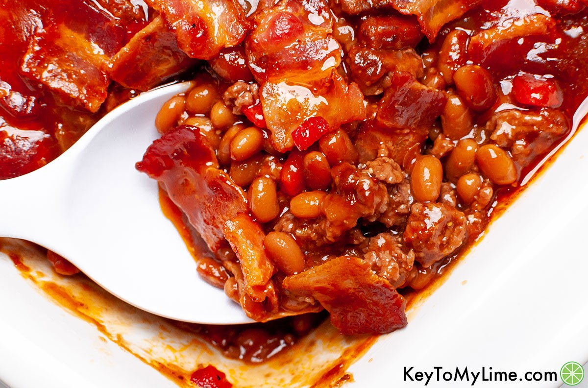 A spoon scooping out a serving of baked beans with ground beef.