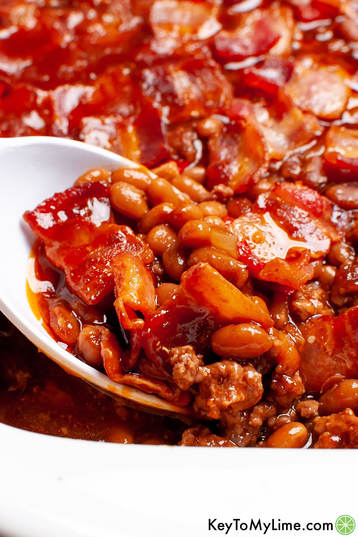 A serving spoon scooping out a portion of baked beans from the casserole dish.
