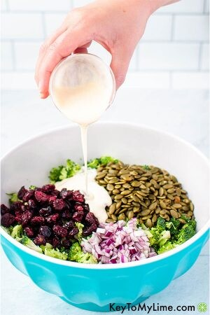 Dressing being poured into a bowl of broccoli salad.